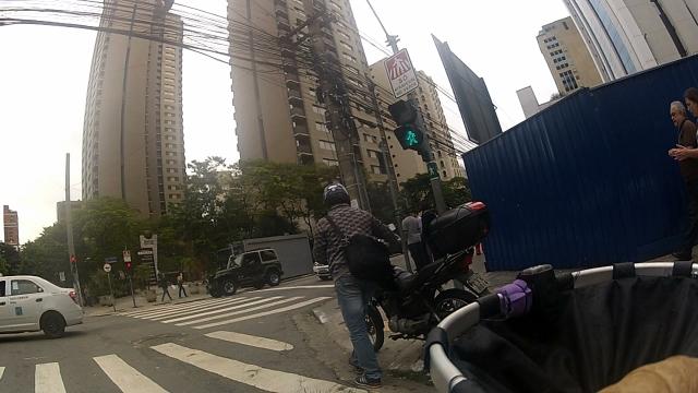 motociclista empurra moto pela calçada, numa boa